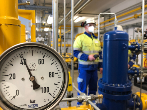 """""""planet e.: Wundermittel Wasserstoff - Bringt die saubere Energie mehr Klimaschutz?"""": Gasnetz für Wasserstoff-Nutzung? Blaue und gelbe Gastanks in einer Versorgungszentrale mit einem Druckanzeiger im Vordergrund. Im Hintergrund ein Arbeiter in Arbeitskleidung."""