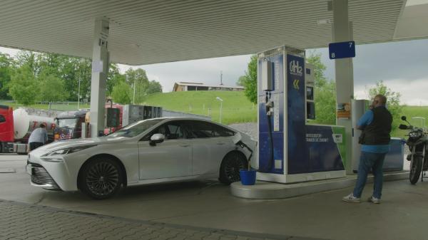 """""""Unter Druck: Wasserstoff in der Mobilität"""": Ein Mann tankt Wasserstoff für einen weißen Toyota Mirai an einer OMV Tankstelle."""